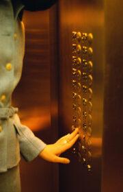 Businesswoman Pushing Elevator Button Probably New York, New York, USA